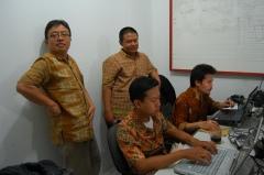Vier mannen dragen een batikoverhemd op kantoor.