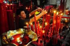 Een Chinees-Indonesische man brandt kaarsjes voor het Chinees nieuwjaar in Pontianak (West-Kalimantan).