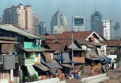 Een sloppenwijk in Jakarta, met op de achtergrond nieuwe wolkenkrabbers