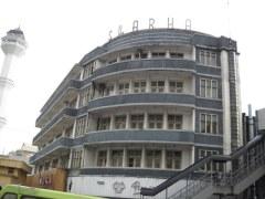 Het verlaten gebouw van Hotel Swarha staat direct naast de Grote Moskee van Bandung; de minaret is op de foto te zien.