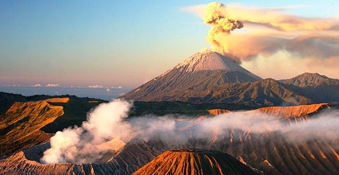 Zowel de Semeru (achter) als de Bromo (linksvoor) spuwen rook uit tijdens de zonsopkomst.