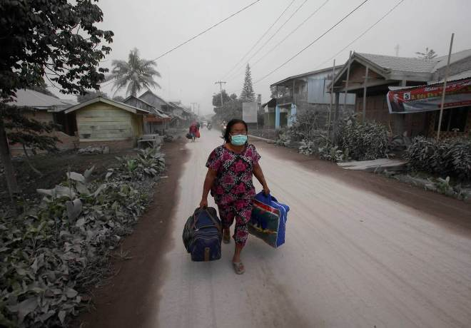 Een bewoonster van het dorpje Payung slaat op de vlucht voor de vulkaan.
