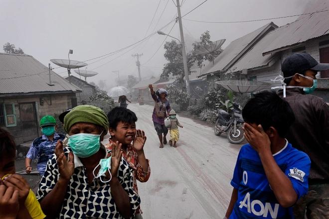 Meer bewoners van het dorp Payung vluchten voor de vulkaan, en gebruiken gezichtsmaskers om zich te beschermen tegen de aswolken.
