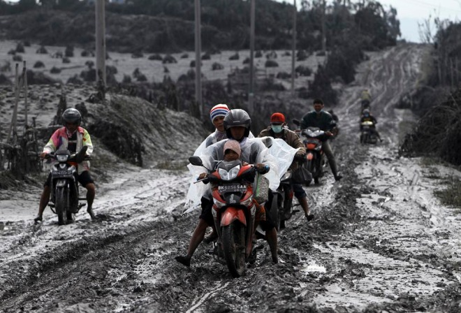 De lokale bevolking van het dorpje Sigarang-Garang vlucht uit het gebied per scooter. De weg is bedolven onder een dikke laag as.