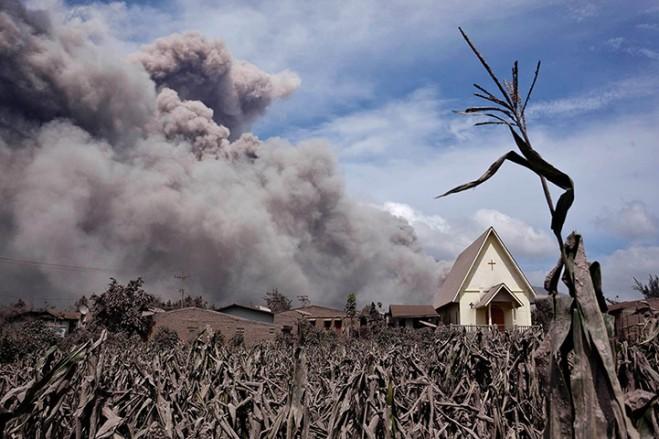 De aswolken van de Sinabung-vulkaan, met op de voorgrond de kerk van het dorpje Sibintun.