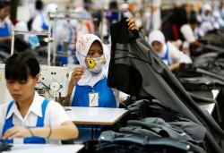 Worker holds part of a pair of trousers at PT Trisula Garmindo Manufacturing in Bandung
